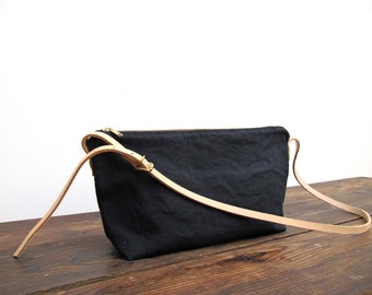 Sale now 25% off.  Black washed canvas crossbody bag. Nude leather adjustable skinny strap with brass buckle. A perfect every day bag.