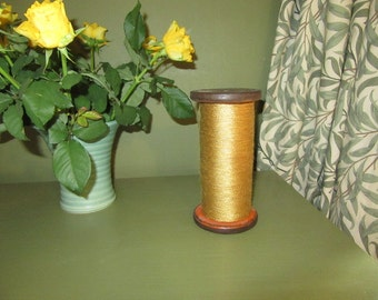 Very large vintage wooden bobbin with gold thread