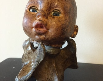 Creepy baby doll head light on a stained cow vertebrae