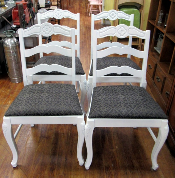 Four white chairs with black upholstery and flower carving detail