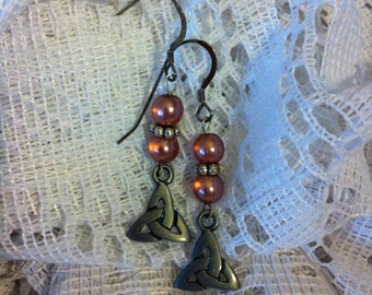 Rose color glass and silver pierced earrings with Trinity knot charms.
