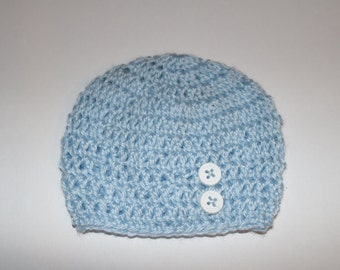 Knitted blue baby hat with white buttons