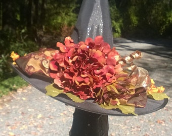 Black Witch Hat, enhanced with silk flowers and orange and rust ribbons.