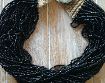 COLIER of 40 strands of glass beads, black with yellow coton balls