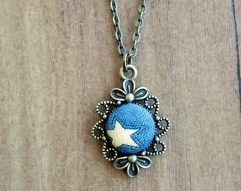 Antique bronze color and detail charm necklace in blue fabric with stella.
