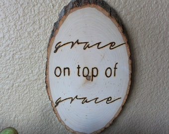 Grace on top of grace – oval wood slice
