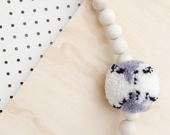 Pom pom and wooden bead wall hanging/garland in a black, white and grey colour palette