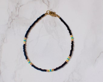 Black Seed Bead Bracelet with Baby Blue, Gold, and White Accents