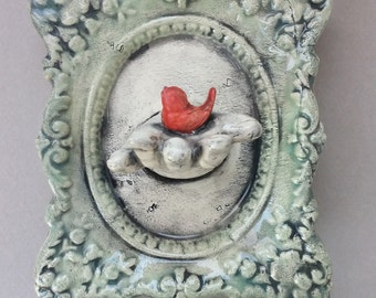 Doll Hand Frame - doll with red bird wall sculpture, ceramic frame