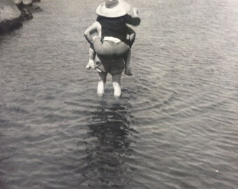old black and white photo of woman getting a piggy back ride in the middle of a creek