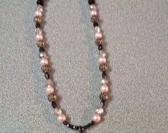 Romantic necklace with pink pearls, silver rose and black beads.  Pendant is lacy medallion with rhinestones.