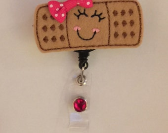 Cute Bandaid Badge Reel with Polka Dot Bow and Gemstone!