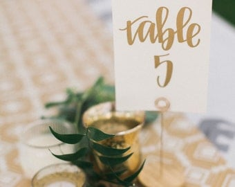 gold calligraphy wedding table numbers // handwriting in calligraphy font for wedding decor // table signs for wedding guest tables