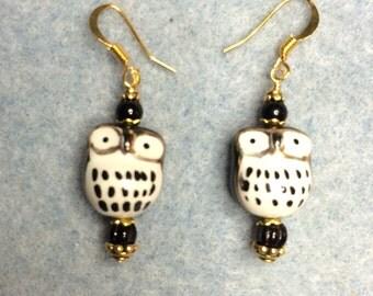 Black owl ceramic bead dangle earrings adorned with black Czech glass beads.