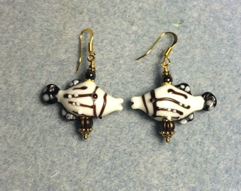 Brown and white striped lampwork kissing fish bead dangle earrings adorned with brown Czech glass beads.