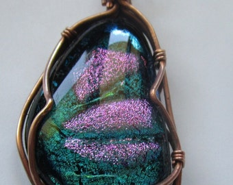 Dichroic Glass wire wrapped  pendant. Two by one and quarter inch.  It is wrapped in Copper.