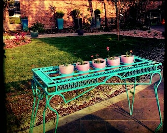 Plant table. Decorative plant stand. Colourful garden furniture.