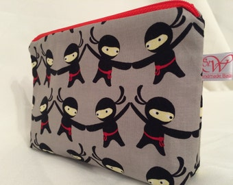 Ninja fabric small make up bag with black waterproof lining and a red zip.
