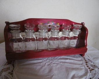 Shelf has fuschia wooden spice and its 6 bottles in clear glass. Vintage 80s romantic deco, vintage, colorful, boho