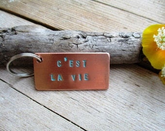 Hand made handmade keychain/tag of copper with text ' CEST LA VIE ' coloured with patina