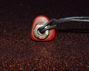 silver mini donught pendant oxidized and set into glass heart .