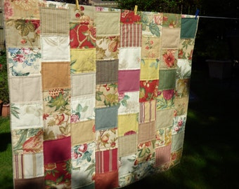 Patchwork quilt, lap quilt, sofa throw. Co-ordinating designer fabric samples randomly pieced. Tan, red, green. Handquilted. Plaid backing