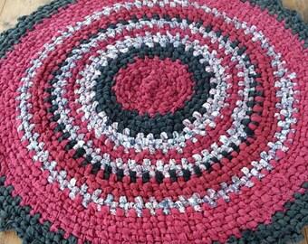 Burgundy and black round rag rug. 83cm across.