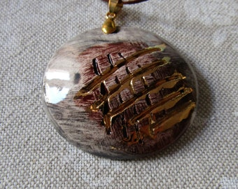 Cooking, handmade ceramic pendant, third fire with gold luster.