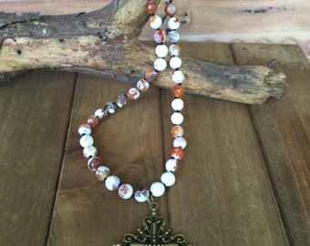 Knotted bead necklace with antique bronze cross