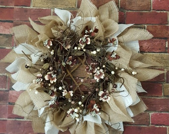 This is a hand made brown and cream burlap wreath. Accented with  brown and cream beads with small brown and cream flowers .