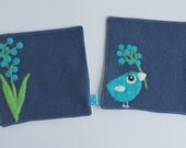 Set of two blue wool fabric coasters with needle felted turquoise blue flowers and birdie bird