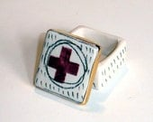 tiny black and white porcelain box with underglaze pattern and bright gold luster