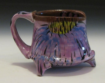 Purple mug with cone flower design and three feet