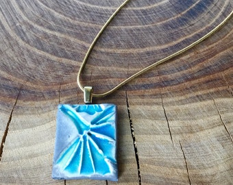 Raku Ginko pendant on a brass chain.