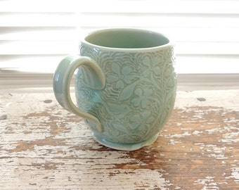 Handmade Stoneware Cup in Pale Green with Hand Carved Lacy Flowers and Birds