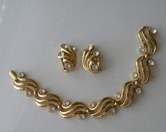 Trifari clear rhinestone swirl clip-on earrings and bracelet. Set.