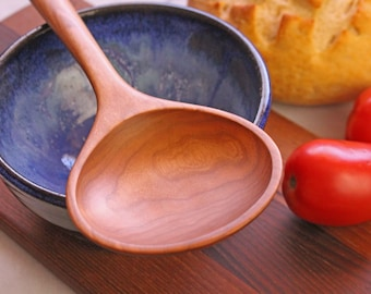 This is a wide wooden spoon for serving and stirring made from Black Cherry wood