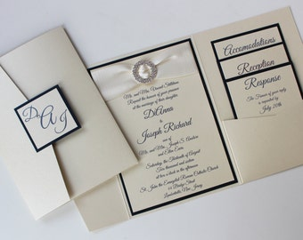 Ivory and Navy Metallic Himalaya Pocketfold Wedding Invitation with Monogram Fastening Label; circular rhinestone buckle