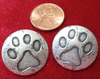 """Pair of metal buttons, 0.75"""" inches across, indented paw print design on top, silver toned, self shank. HMFR13.6-19.10."""
