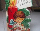 Colorful 1950's embossed die cut gold gilded unused Carrington christmas angel w/ full tummy holds candy cane asleep against red candle tree