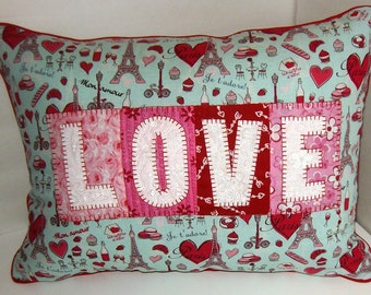 Embroidered L O V E pillow with red piping