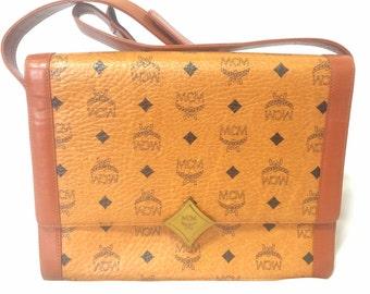 Vintage MCM brown monogram square shoulder bag with leather straps and golden star shape logo motif closure. Designed by Michael Cromer.
