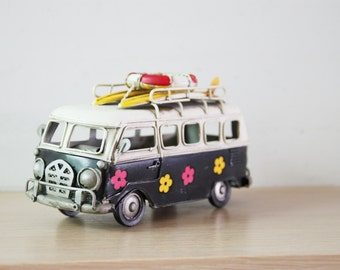 Retro VW van, hippie van in blue black and creamy white with painted flowers and surfboards on the baggage rack, VW collectible miniature