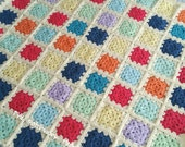 Hand made crocheted baby blanket featuring bright coloured granny squares on a cream background 78x78cm/31x31inches square