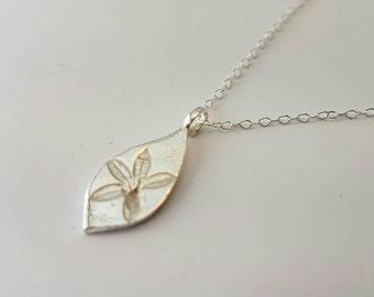 Pressed blossom silver pendant