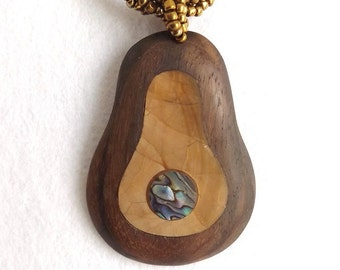 Real abalone and shell pear shaped two tone wooden necklace. Layers of natural shell fragments. Gold coloured twisted bead rope style chain.