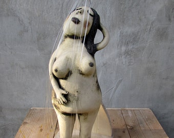 Ceramic lady in the shower with a pair of hand carved wood slippers
