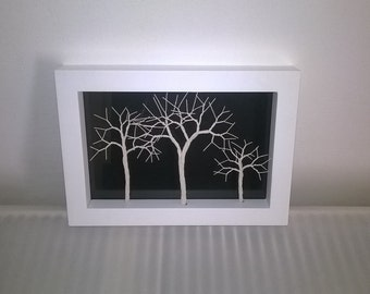 Ivory wire trees in a white picture frame.