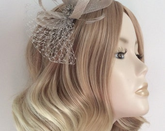 PUTTY GREY FASCINATOR, with fine netting, feathers, and silver flower, on a 9cm clip