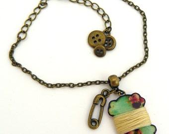 Dressmaker bracelet spool of thread resin cardboard, pin nursemaid and buttons